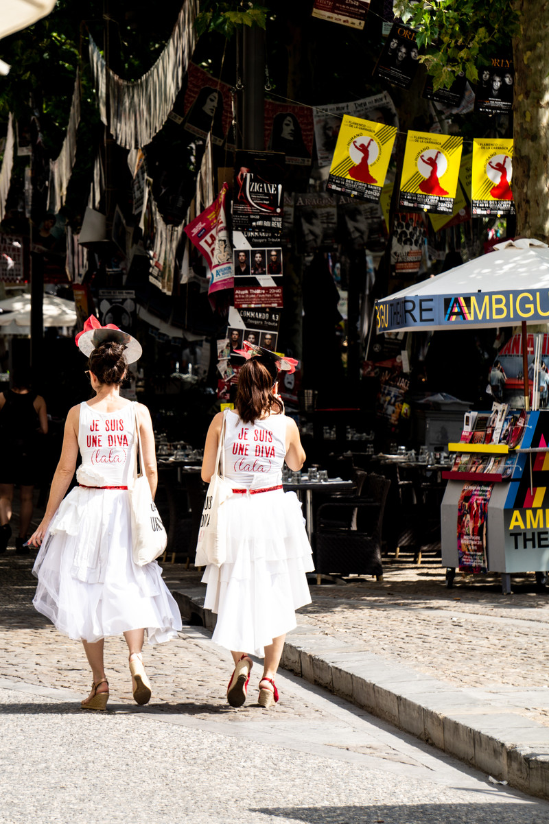 Two women stroll through the streets of Avignon