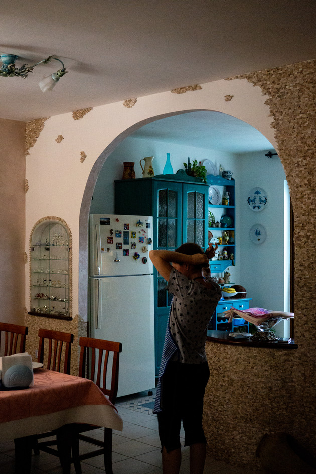 A Sardinian woman ties her apron in her kitchen.