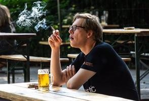 A man enjoys a smoke at a beirgarten