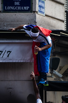 Parisians climb up buildings to get a better view of a bar's TV showing the World Cup