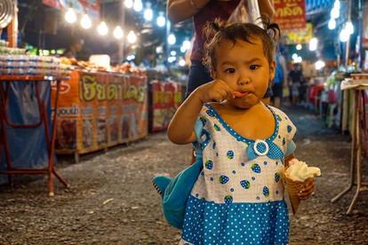 A little girl enjoys ice cream at a night market.