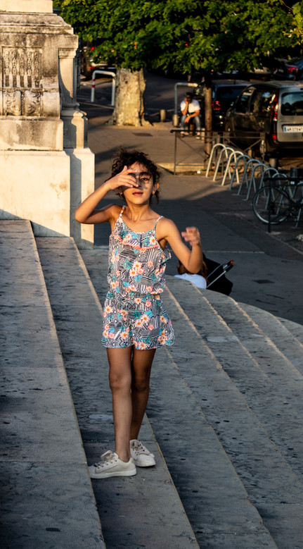 A girl shields her eyes from the sun.