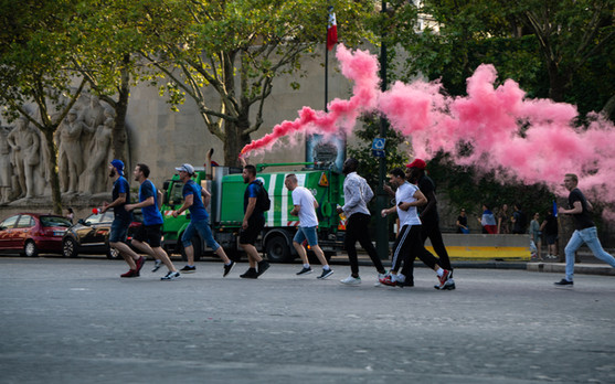 Parisians cheer on the French soccer team with colored gas.