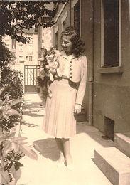 une jeune femme debout regarde et porte un chien