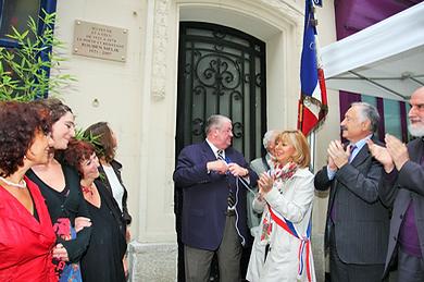 9 personnes devant la porte d'une maison , drapeau tricolore plaque sur la façade