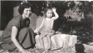 une femme agenouillée et un enfant assis sur une pierre lève le bras