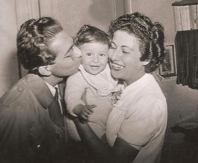 un bébé entre un homme qui l'embrasse et une femme qui sourit