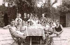 photo d'enfants assis autour d'une tableavec adultes dans le fond