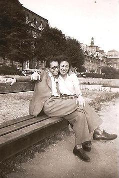 un homme et une femme assis sur un banc dans un jardin