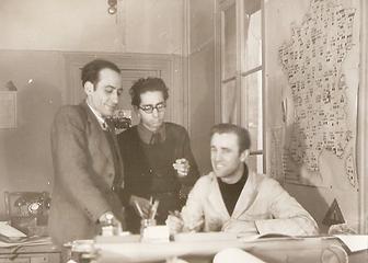 3 personnes , 2 sont debout 1 est assise, carte de France et fenêtre à droite