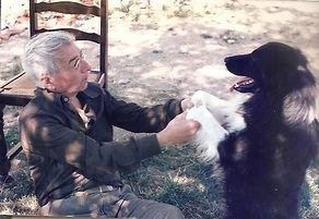 Rouben Melik assis tient les 2 pattes d'un chien