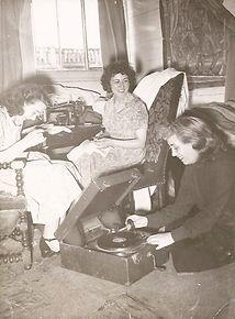 3 femmes une agenouillée utilise un tourne disque , les 2 autres assises font de la couture