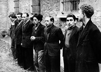 8 hommes debouts contre un mur et des fenêtres avec barreaux
