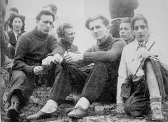 4 jeunes gens et une femme adultes assis par terre