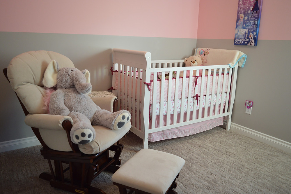 Baby's nursery scence, white cot and a padded nursing chair with a stuffed elephant cuddly toy on it