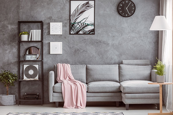 Grey couch with light pink throw blanket.