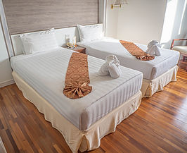 Pair of hotel beds with grey striped sheets, a tan embroidered runner, and a folded towel.