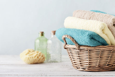 Whicker basket with blue, yellow and beige towels in it.