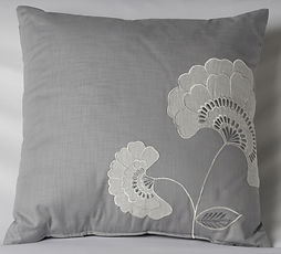 A gray pillow embroidered with flowers