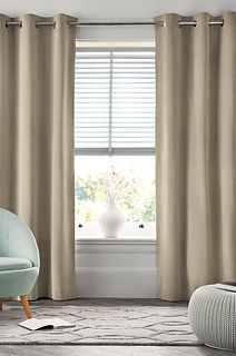 A large window with beige curtains