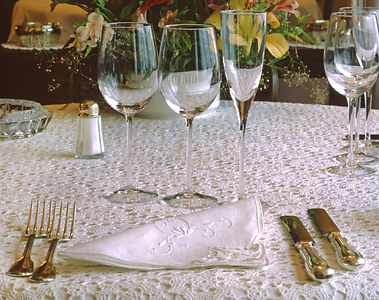 Wine glasses, an embroided napkin,and gold colored utensils