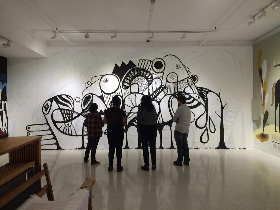 Four people viewing a stylized black and white unfinished mural on a wall.