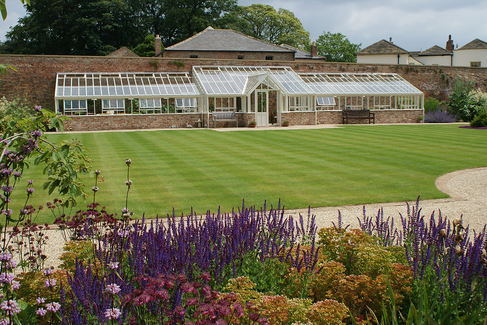 New glasshouse in walled garden with lawn and perennial planting in North Yorkshire in walled garden designed by Alistair Baldwin