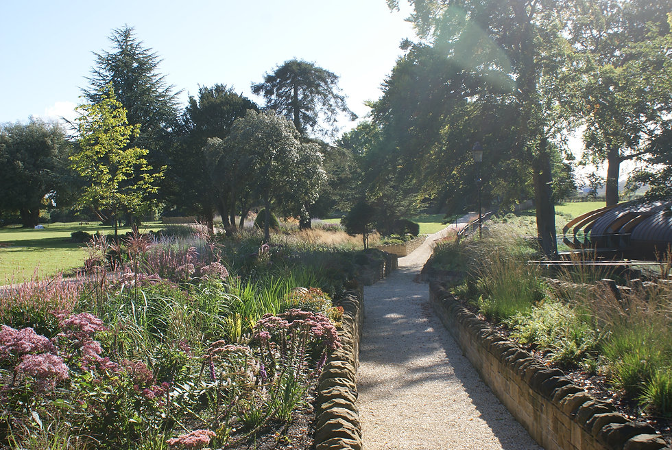 Drifts of perennial planting in raised beds along the gravel path leading to the Blackburn Wing