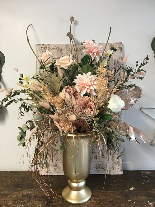Boho dried and faux flower display in a gold urn