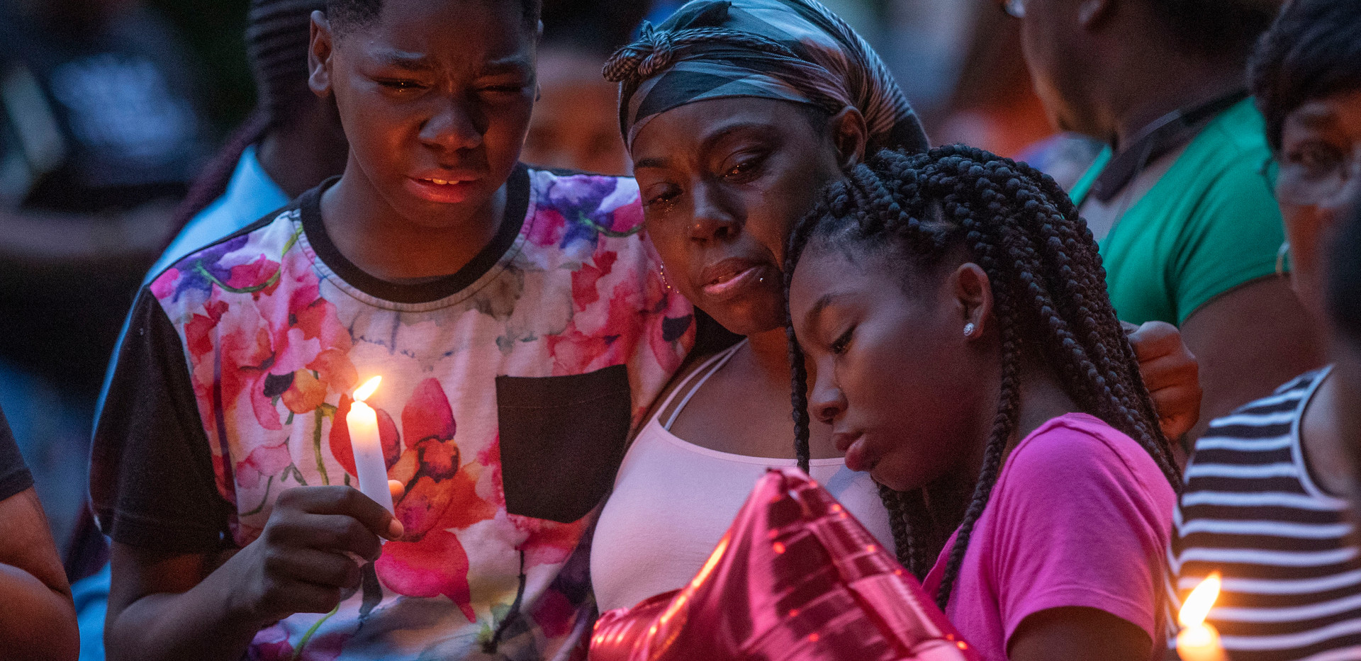 A crowd gathers as a candlelight vigil is held honoring Malik Jackson, 21, who was stabbed and killed on Wednesday, May 27, 2020. Jackson's younger brother cries as he holds a candle and stands with their mother Jennifer Jackson.