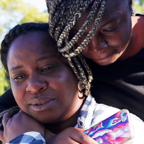 Tiffany Zachery, mother of 16-year-old Amarion James who was shot and killed last weekend, grasps her daughter Camiya Williams, 21, as she embraces her from behind. Together they mourn the loss of James.