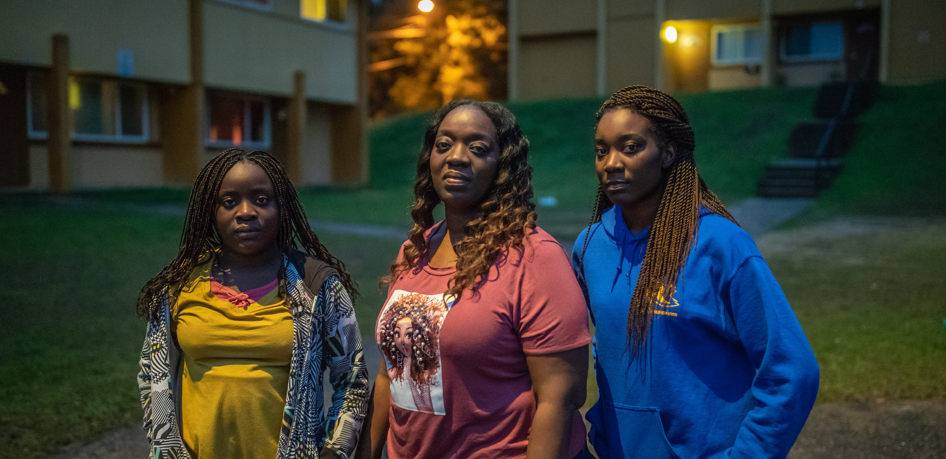 Kisha Simms, 38, center, poses with her daughters Deitra Jackson, 11, and Lynaya Saylor, 18, under the glow of a street light outside their Springfield Apartment residence.