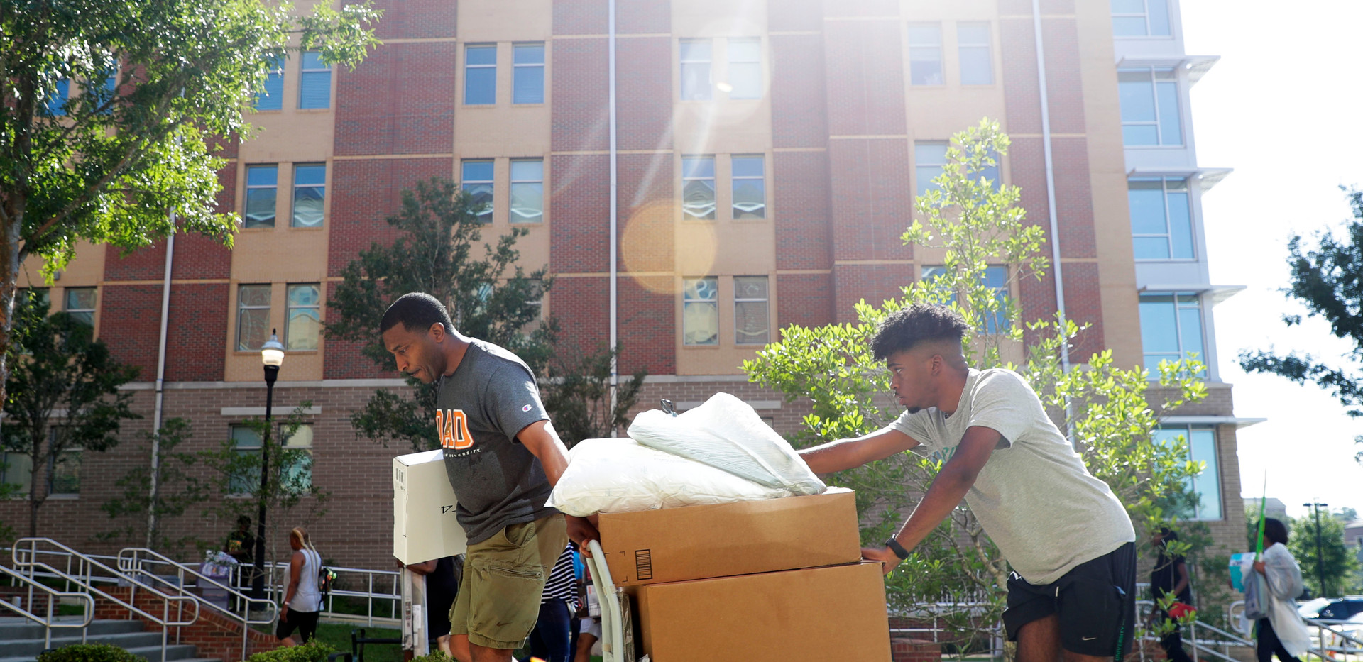 Deadric Hollins, left, and his son Malik Hollins roll a dolly stacked with Malik's belongings as they move him into his freshman dorm room at FAMU Thursday, Aug. 22, 2019.
