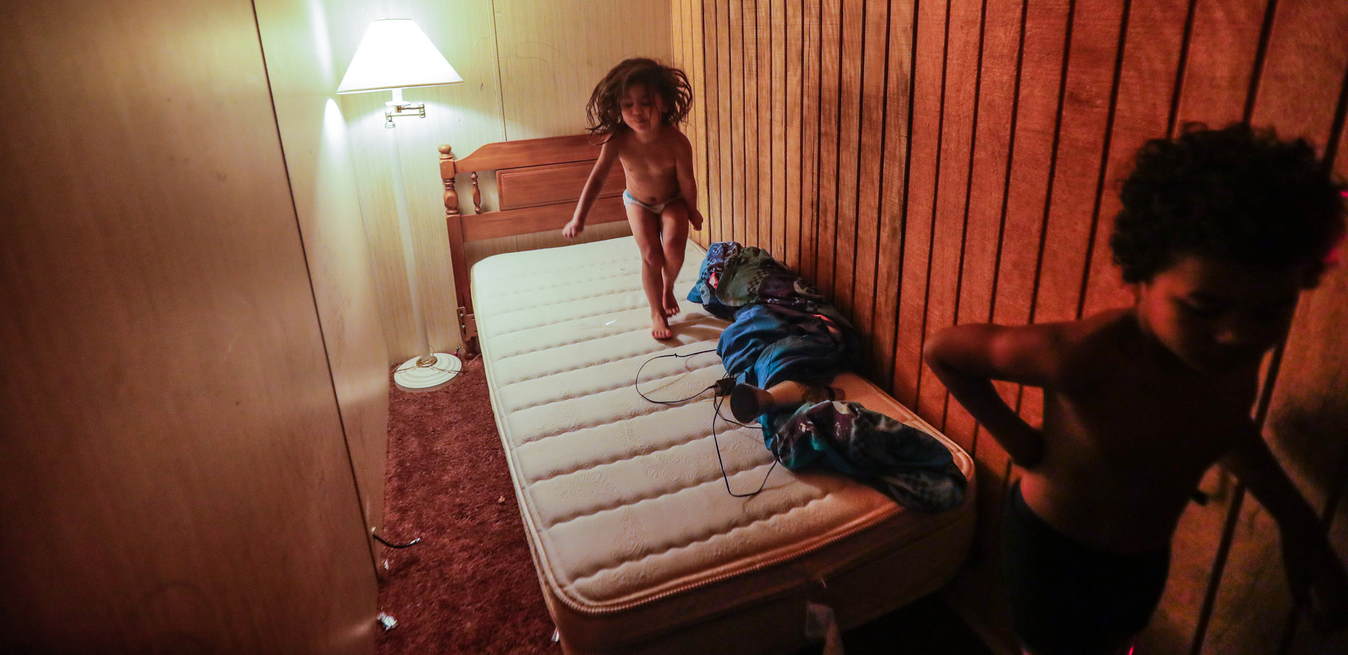 """Zulele """"Victoria,"""" 3, jumps on a twin bed in a bedroom with a wall built to create another bedroom in her family's trailer. Victoria's brother, Romeo, 8, walks through the room as she bounces."""