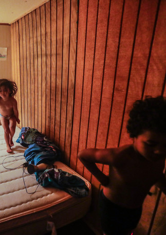 "Zulele ""Victoria,"" 3, jumps on a twin bed in a bedroom with a wall built to create another bedroom in her family's trailer. Victoria's brother, Romeo, 8, walks through the room as she bounces."