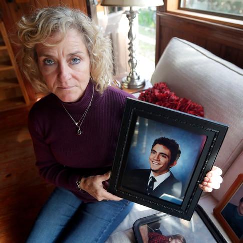 Katherine Gilbert holds a school photo of her son Justin Joseph Dousa-Valdez, 36, who struggled with mental illness. Dousa-Valdez killed himself November 2019.