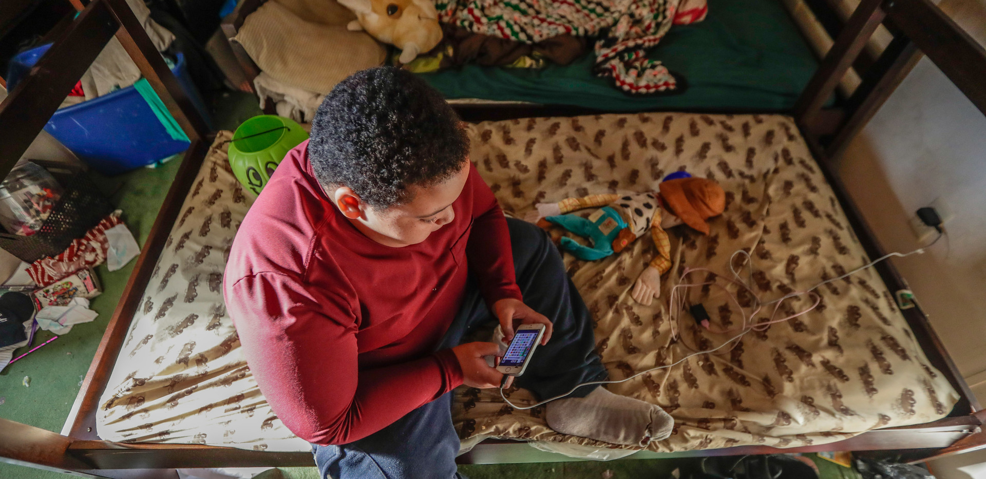 Brandon Hughes, 11, plays games on his phone in his bedroom that he shares with his 9-year-old sister. Brandon and his sister share a trailer with their parents located off of Aenon Church Road.