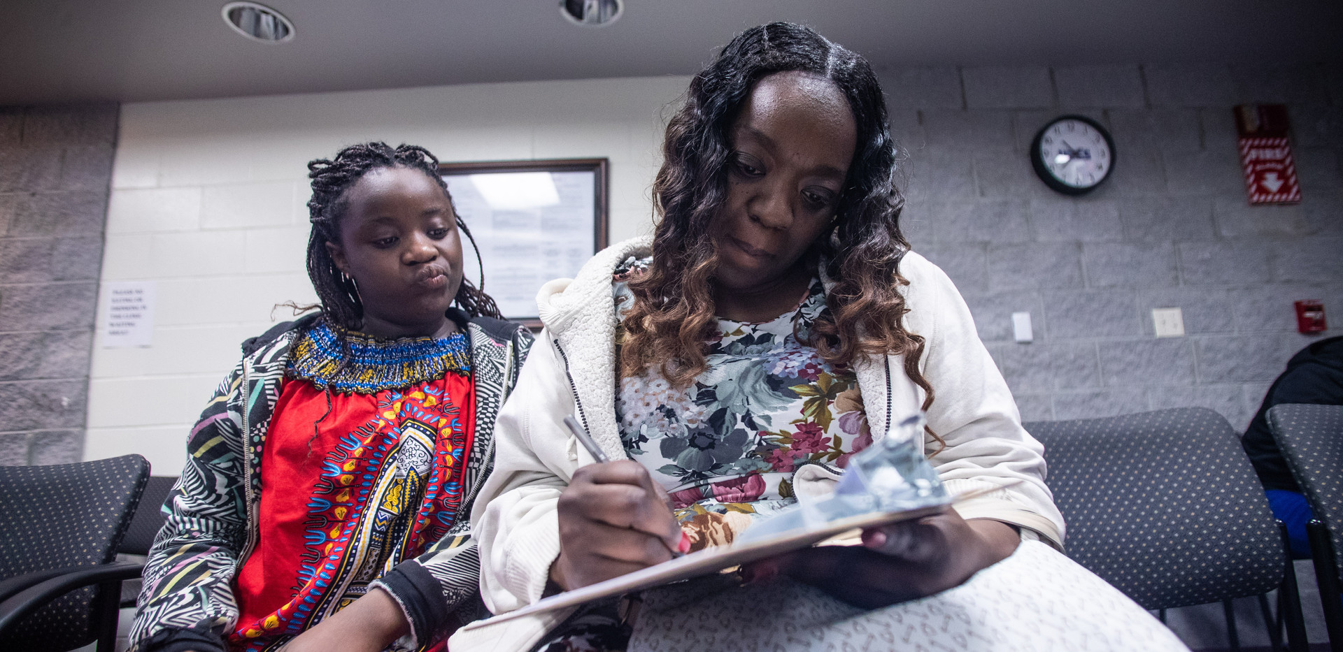"""Kisha Simms, 38, fills out paperwork before her daughter, Deitra """"DeeDee"""" Jackson""""s, 11, dentist appointment at a Neighborhood Medical Center."""