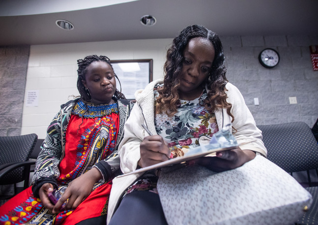 "Kisha Simms, 38, fills out paperwork before her daughter, Deitra ""DeeDee"" Jackson""s, 11, dentist appointment at a Neighborhood Medical Center."