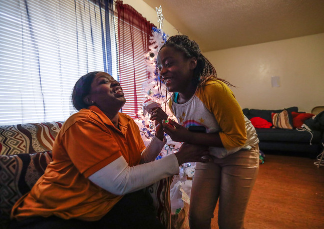 "Kisha Simms, 38, tickles her daughter Deitra ""DeeDee"" Jackson, 11, as they both have an afternoon snack and catch up on each other's day."