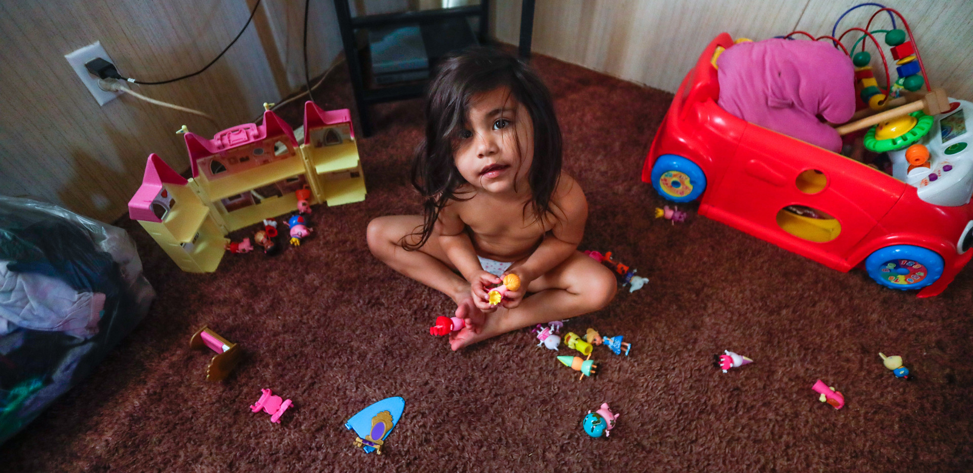 """Zulele """"Victoria,"""" 3, looks up from her toys that she plays with on the living room floor of her family's trailer located off of Aenon Church Road."""