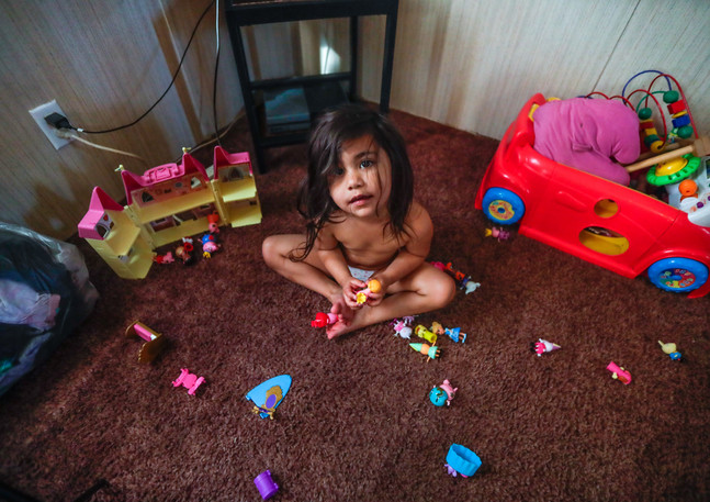 "Zulele ""Victoria,"" 3, looks up from her toys that she plays with on the living room floor of her family's trailer located off of Aenon Church Road."