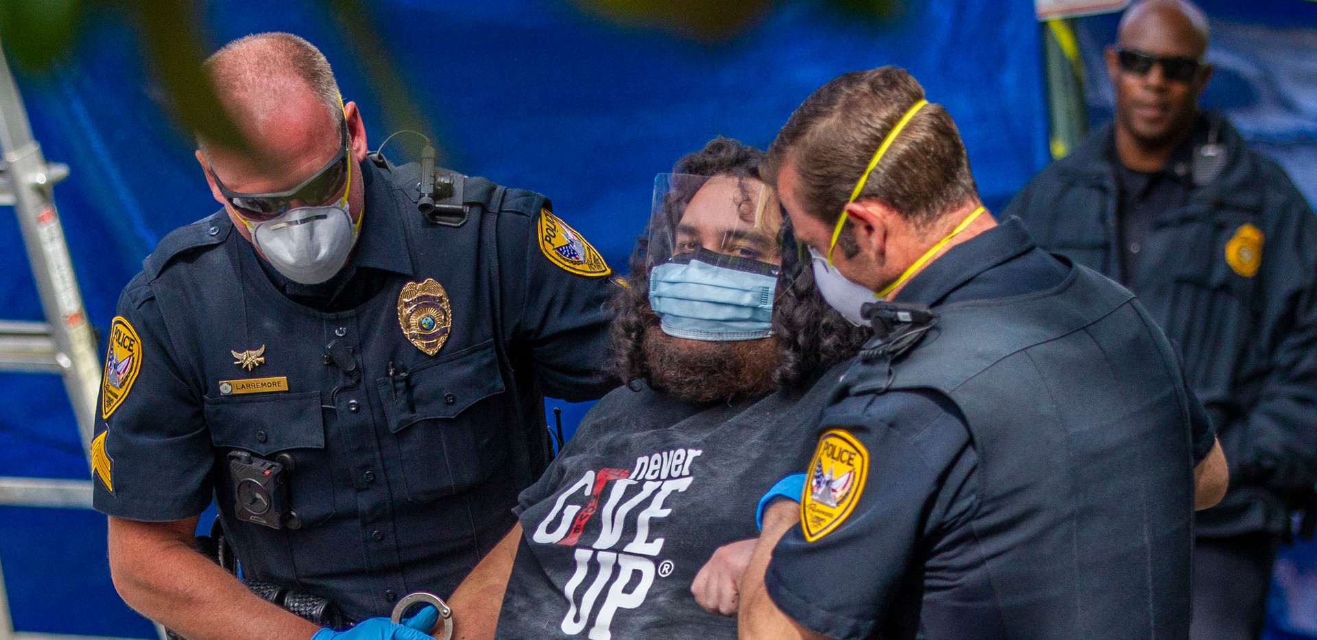 Officers with the Tallahassee Police Department arrest protester Jordan Mazurek, who cemented his hands in two 55-gallon plastic drums in the driveway of the Florida Governor's Mansion, Friday, April 17, 2020. Mazurek protests how Gov. Ron DeSantis is handling coronavirus in state prisons.