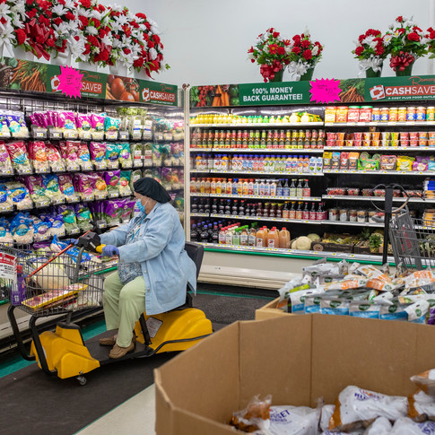 Patricia Williams, 82, pulls a bag of frozen Brussel sprouts as she grocery shops at Ramsey's Cash Saver, located in Blountstown, Florida, March 31, 2020. Williams is a firm believer in wearing gloves and a mask when out in public to protect her from the coronavirus.