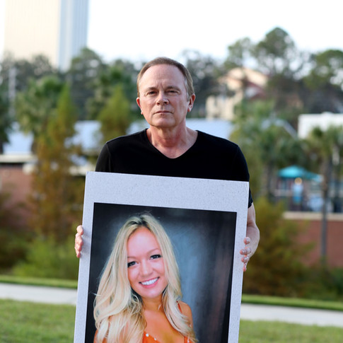 Jeff Binkley, father of Maura Binkley, a Florida State University student killed in a shooting at Hot Yoga Tallahassee, poses at Cascades Park with a photo his daughter, Sunday, Nov. 11, 2018.