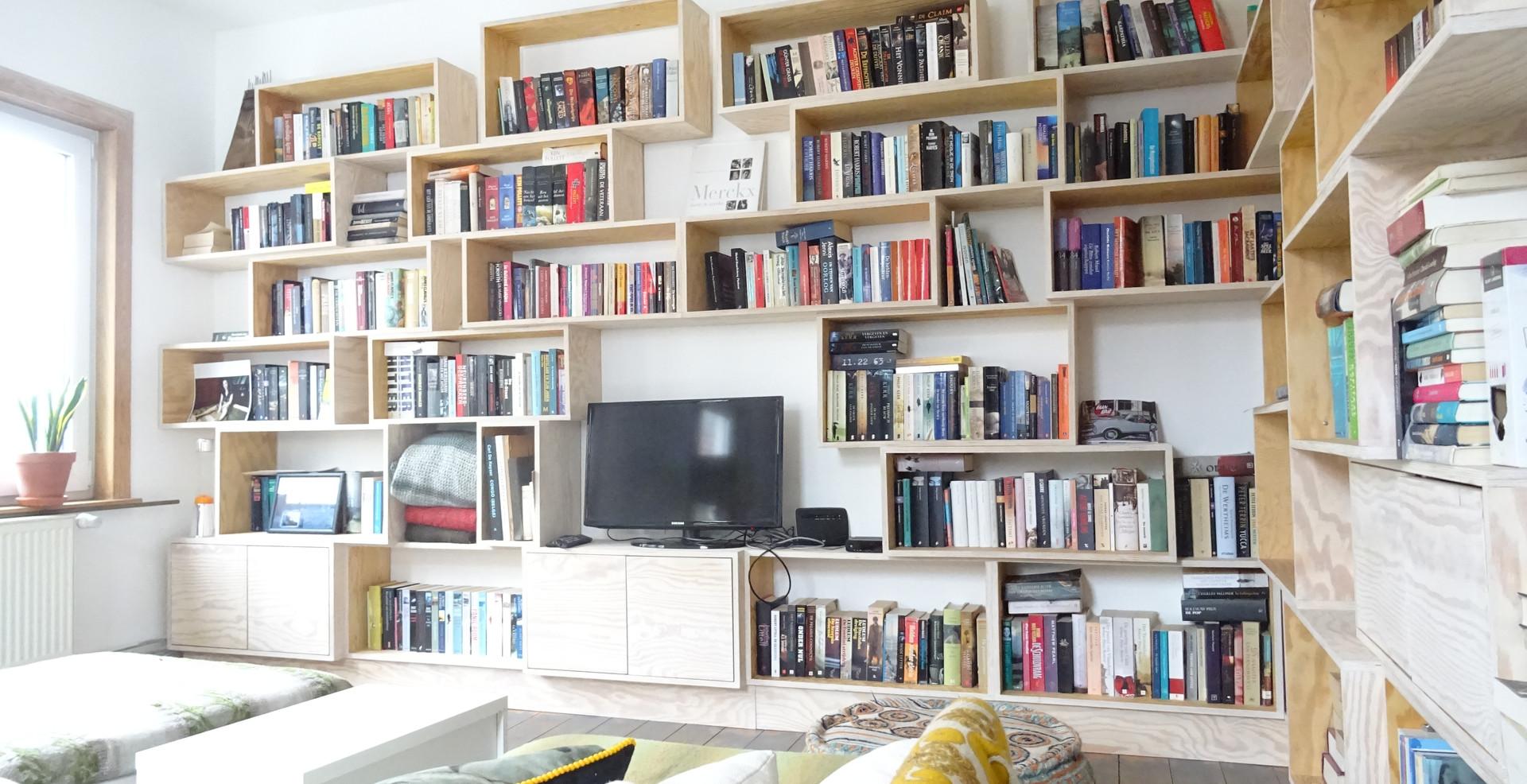 Houten boekenkast open vakken gezellig zetel kleuren mooi licht