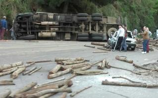 Homem fica ferido ao tombar caminhão e derrubar toras de madeira na Rota do Sol