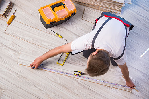 Man laying laminate flooring in construc