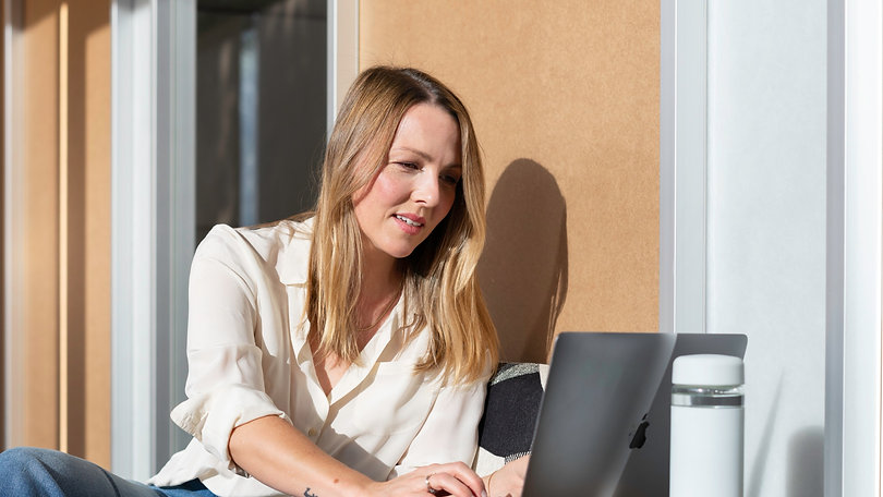 A salesperson working in an office at a laptop in the sun_edited.jpg