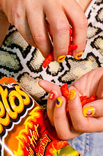 A handful of hot cheetos being eaten by someone with yellow painted nails and an animal print top.